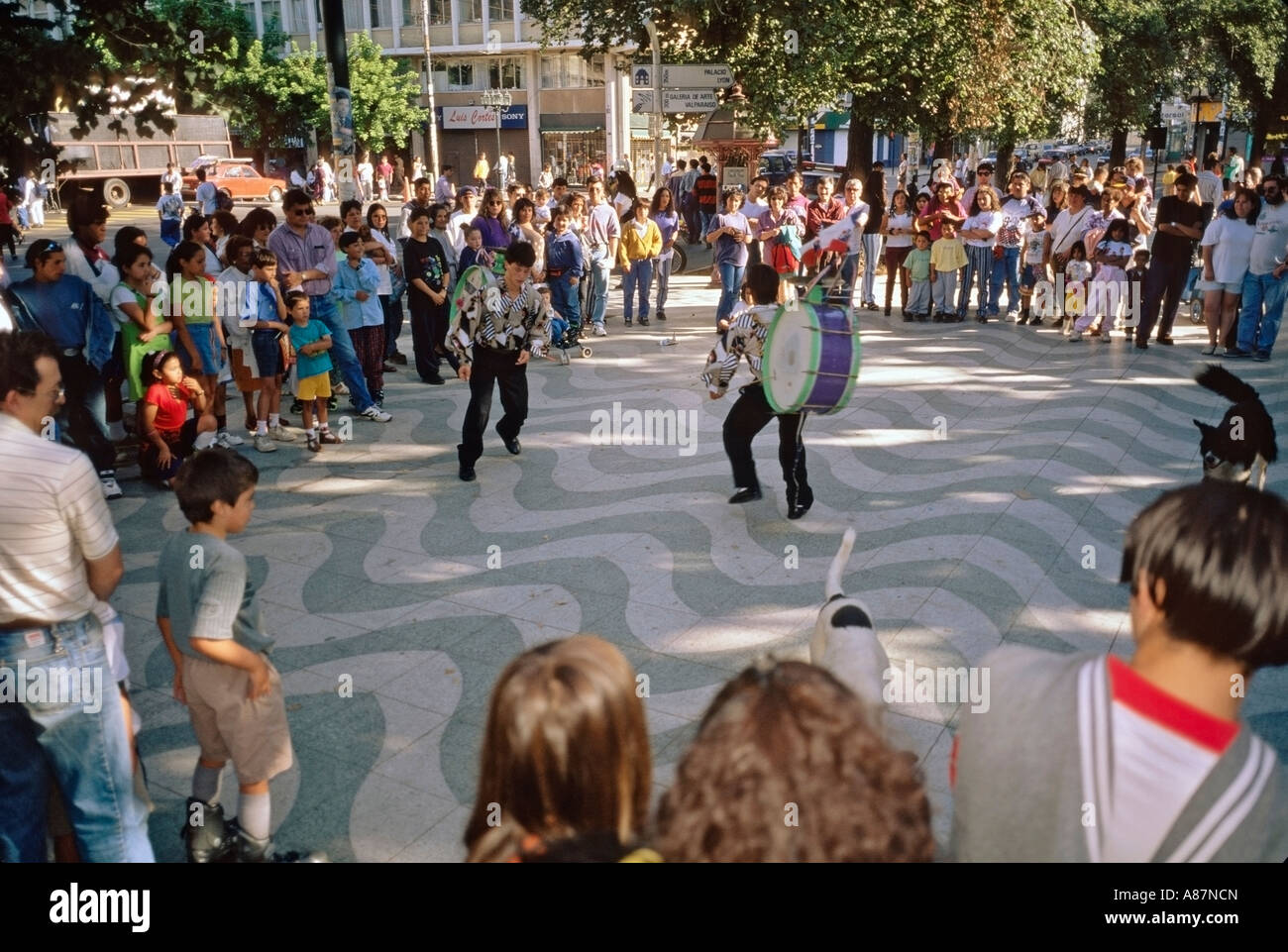 Native Chilean street performers entertain spectators with dancing and bass drums in Parque Italia Valparaíso - Stock Image