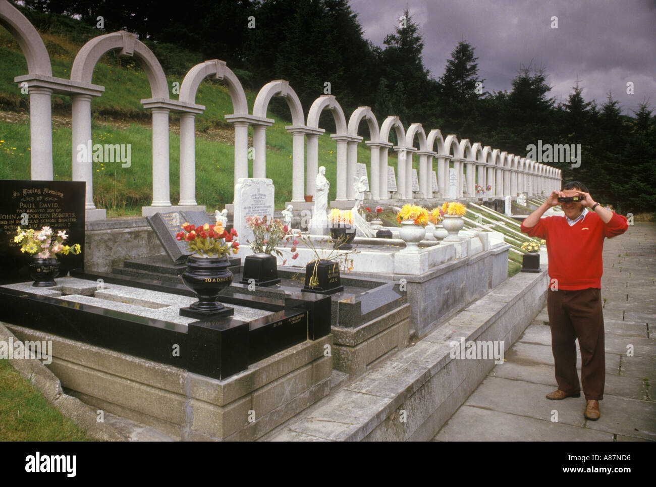 Aberfan Mid Glamorgan A tourist takes a photograph of the memorial to mark the death of children killed in a mining disaster - Stock Image