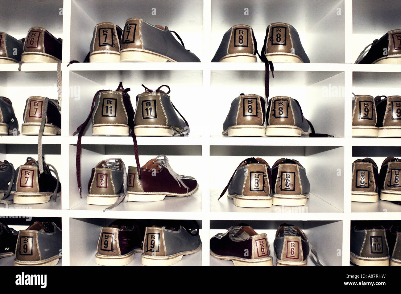 Several pairs of bowling shoes on shelf. - Stock Image