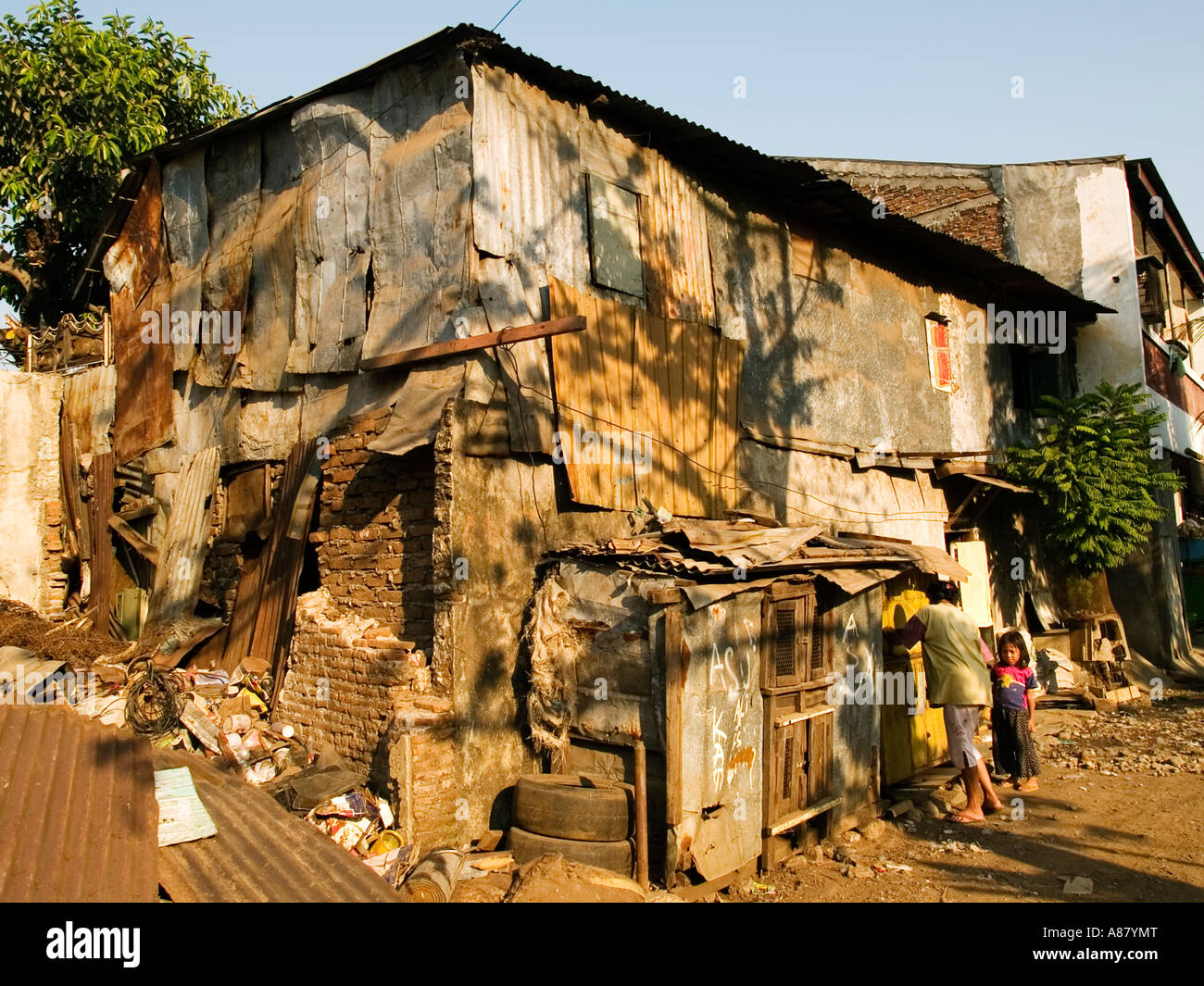 Mother and child enter their ramshackle shack like house in slum area,Surabaya,Java,Indonesia - Stock Image