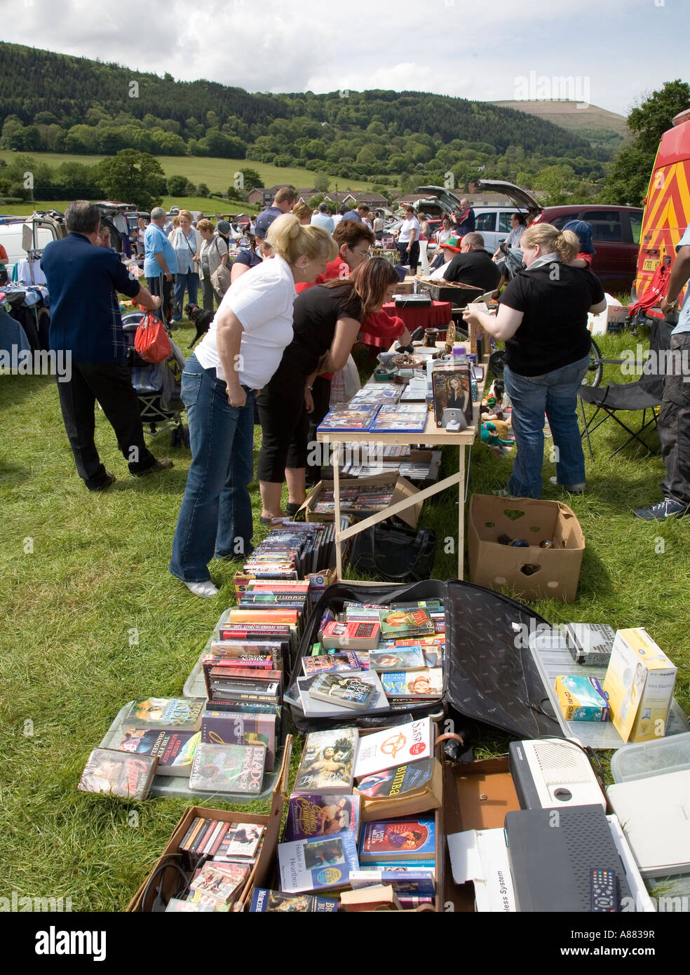Books and household goods on display at car boot sale Wales UK - Stock Image