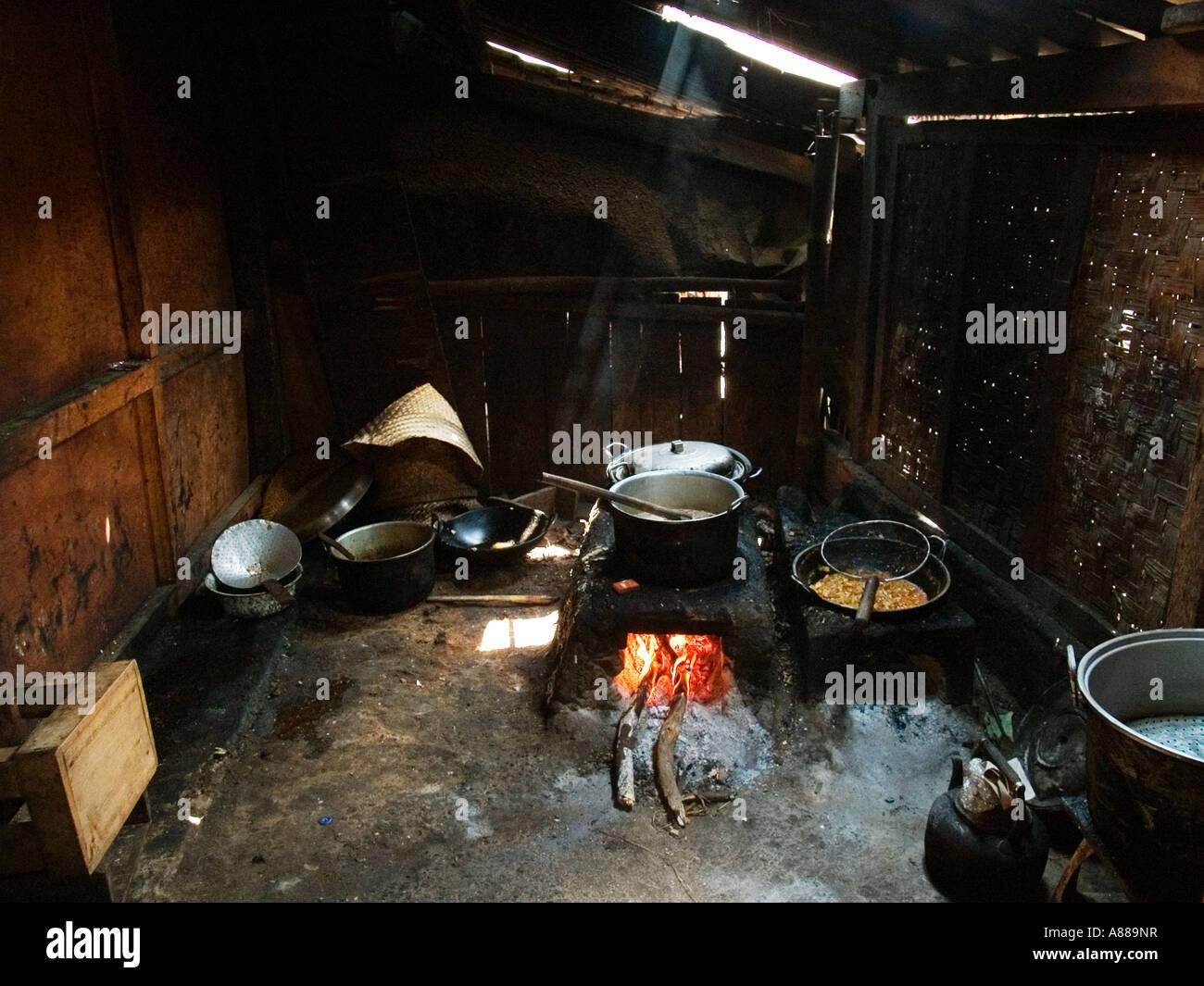 Flames leap around blackened cooking pot in dimly lit rural kitchen,near Madiun,Java,Indonesia - Stock Image