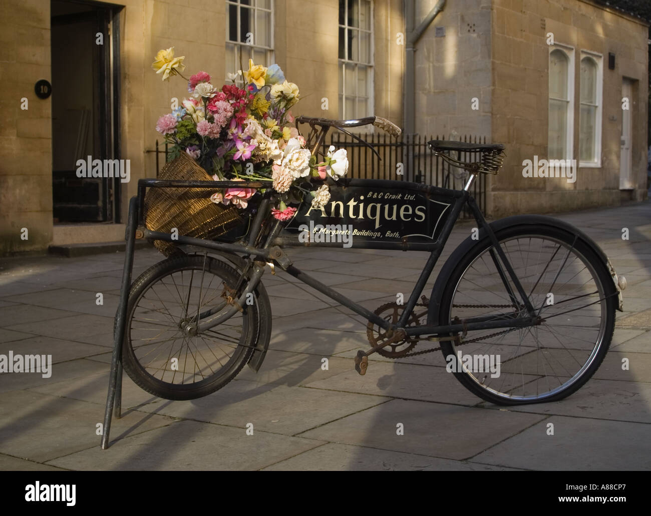 Old bicycle advertising antiques shop in the city of BATH England - Stock Image