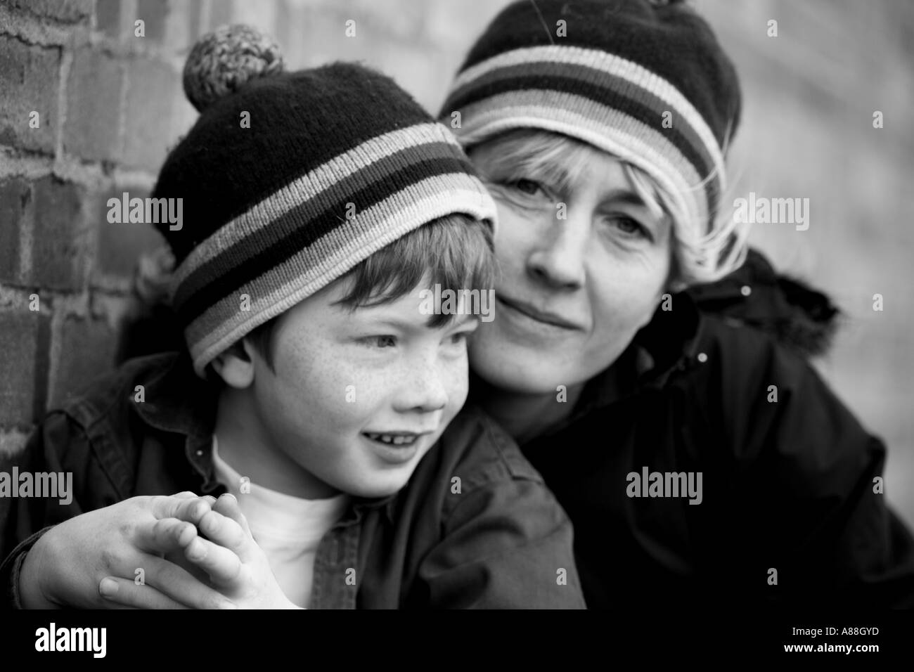 Horizontal black and white portrait of mother with her young son wearing matching bobble hats outdoors in urban setting