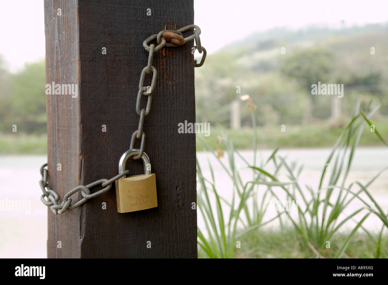 Padlock and chain on a country gatepost - Stock Image