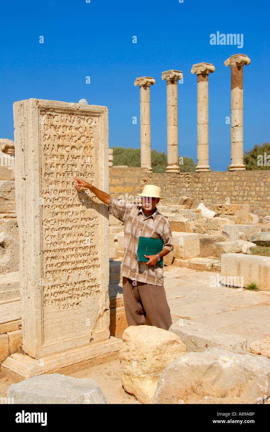 Local guide translates inscription on stone plate old forum Leptis Magna Libya - Stock Image