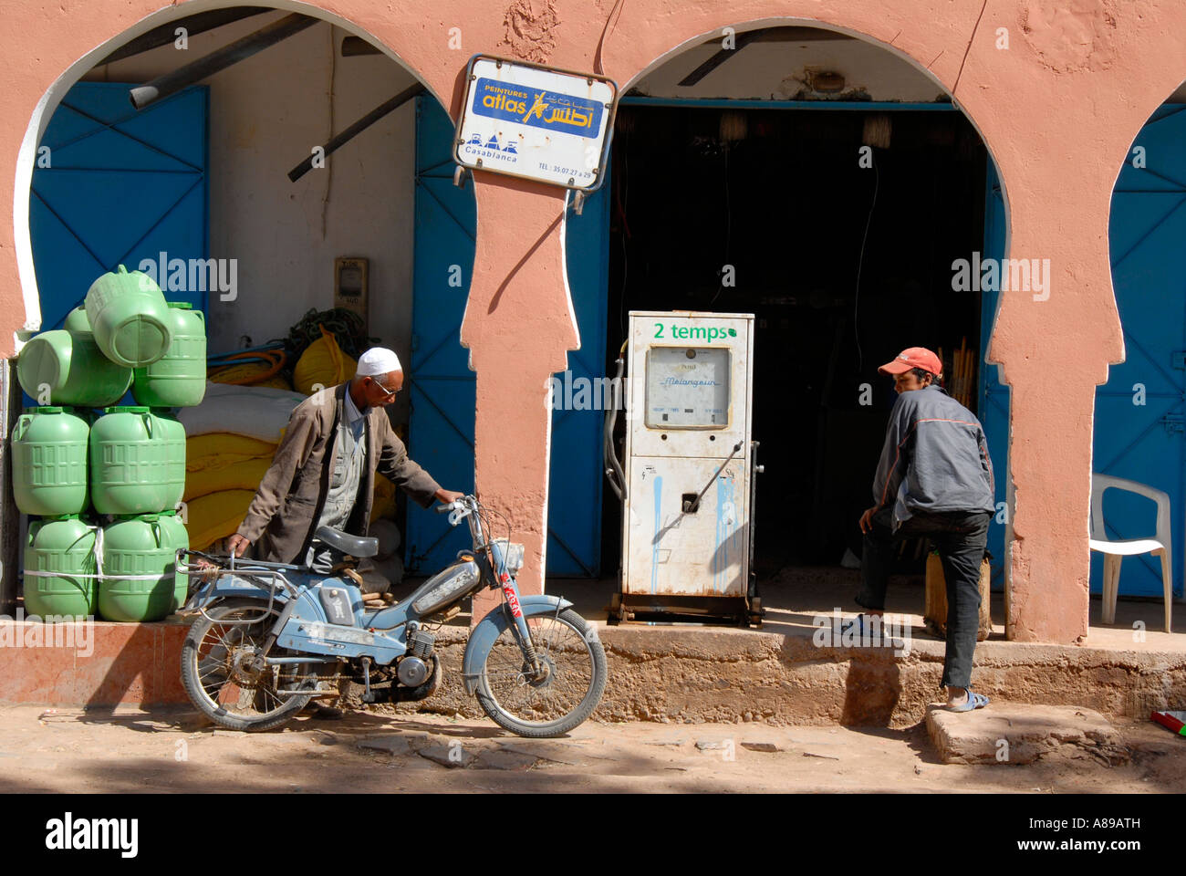 Oriental flair motorcyclist gets gas at old fuel station Foum Zguid Morocco - Stock Image