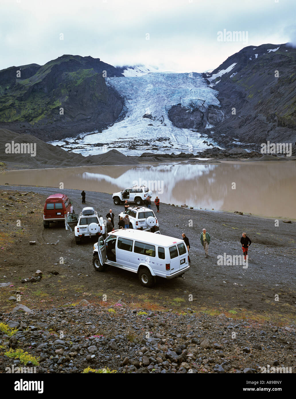 Four wheel drive cars and a glacier lake behind the Gigjoekull glacier, Thorsmoerk, Iceland - Stock Image