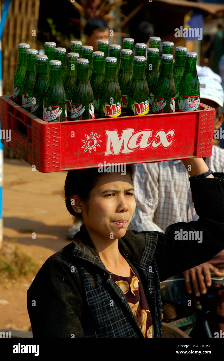 Woman carries cage with lemonade Max on her hat Bago Burma - Stock Image