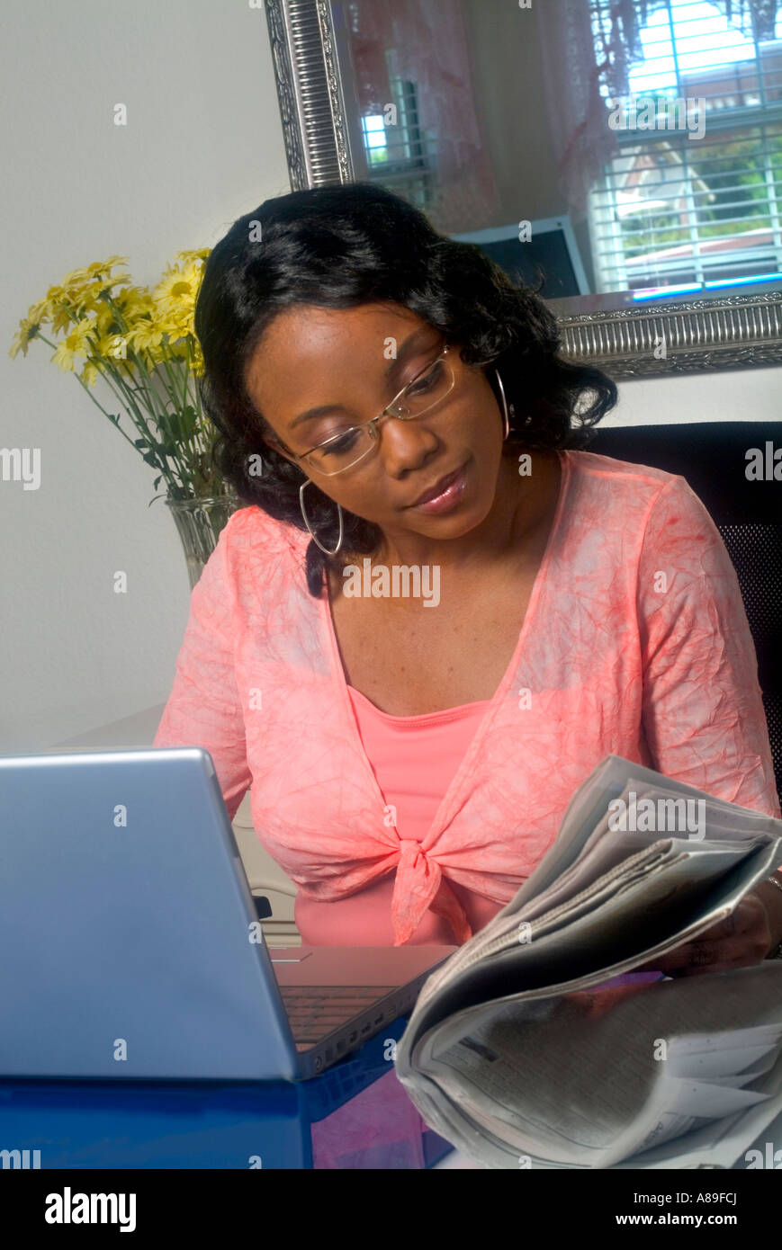 a young pretty ethnic black woman is working on her laptop and stock
