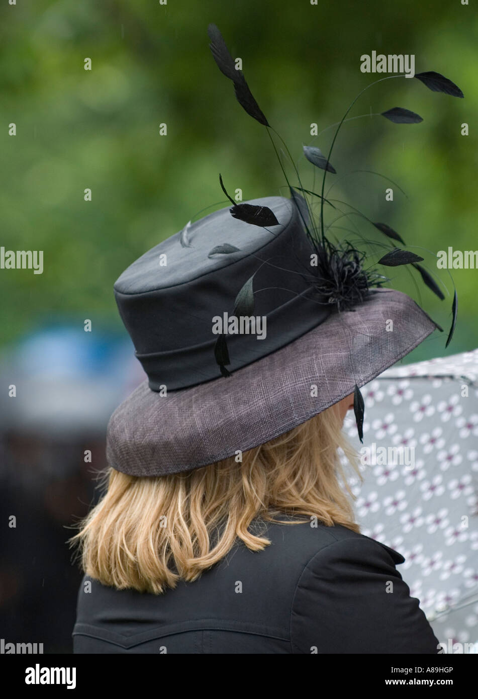 Blonde young woman wearing a black feathered hat - Stock Image