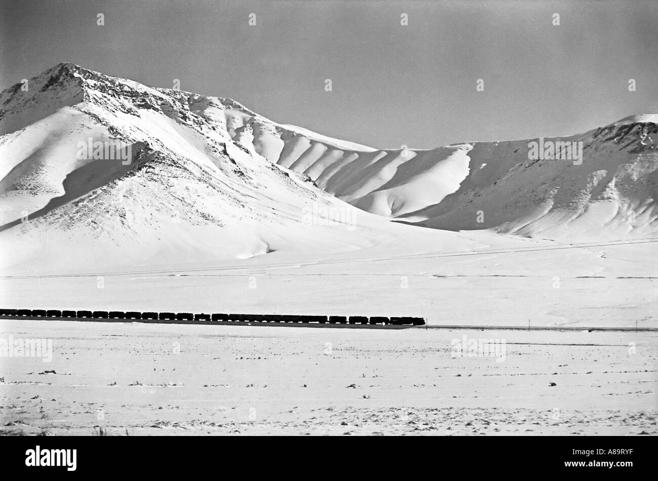 IRAN ARAK Train crossing a snowy plateau in the mountains of Iran Black and white dramatic landscape print - Stock Image