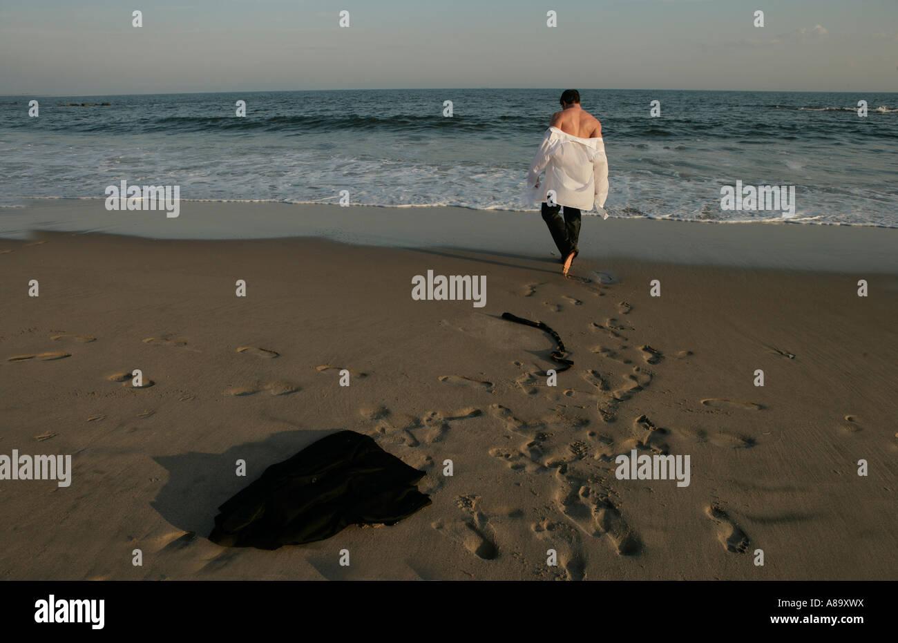 Man walking out to sea - Stock Image