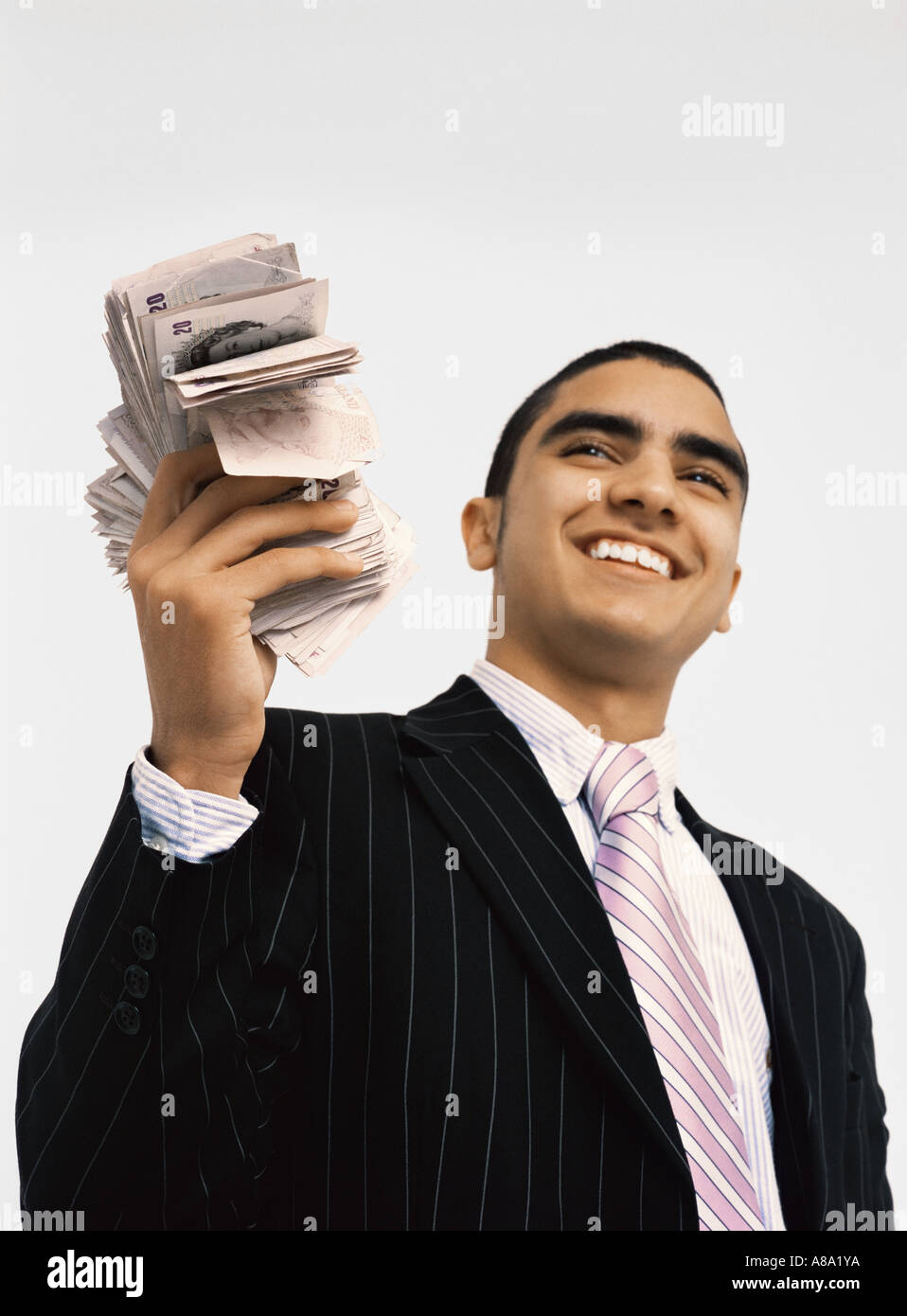 Businessman with wad of cash - Stock Image