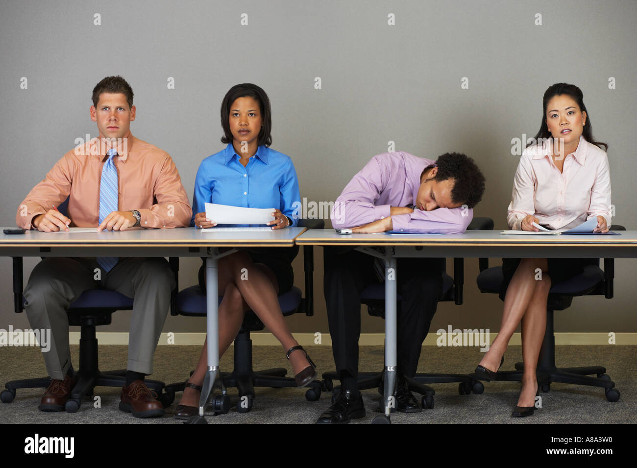 Businessman sleeping during a meeting - Stock Image
