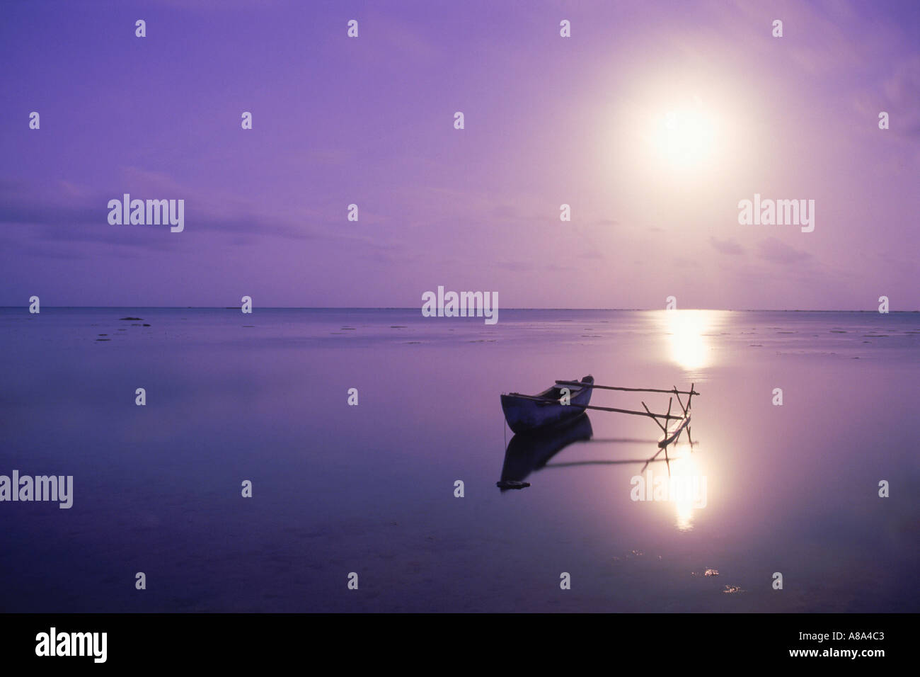 Outrigger in calm lagoon off Aitutaki Island under full moon in South Pacific - Stock Image
