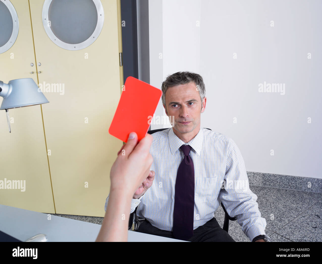 Businessman getting a red card - Stock Image