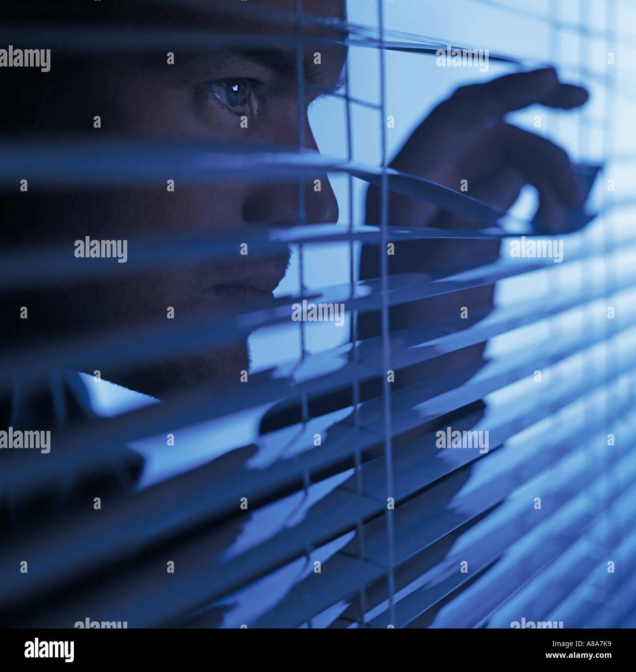 Man looking through blinds - Stock Image