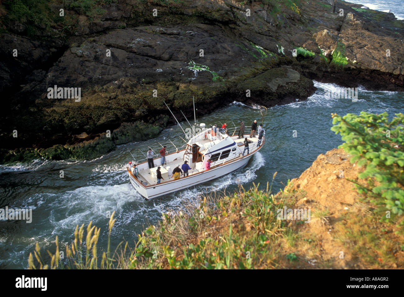 Fishing boat heading to sea between narrow rock channel world s smallest natural navigable harbor Depoe Bay Oregon Stock Photo