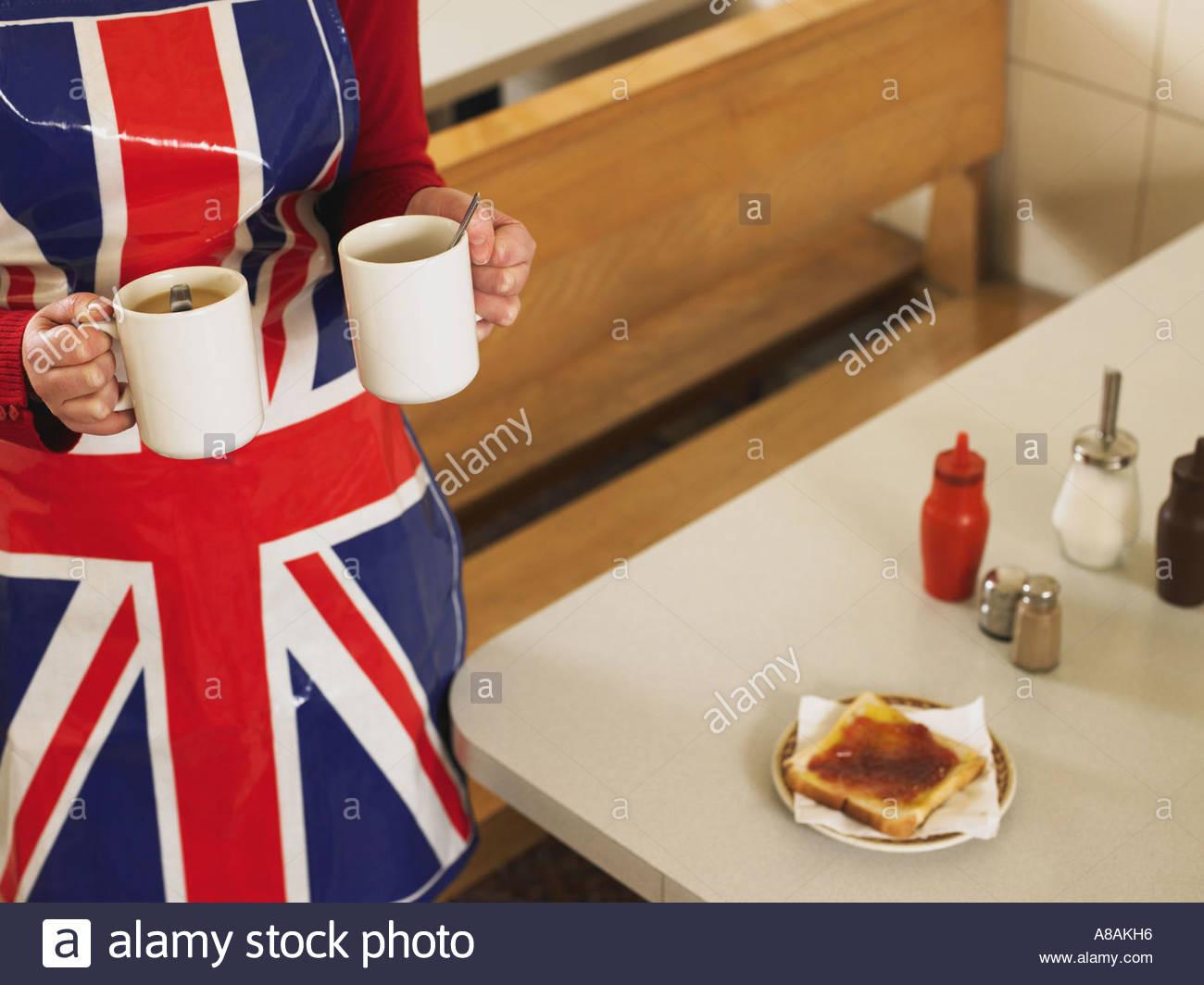 Waitress bringing mugs of tea - Stock Image