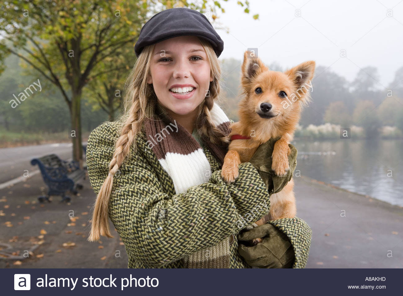 Young woman carrying dog in the park - Stock Image