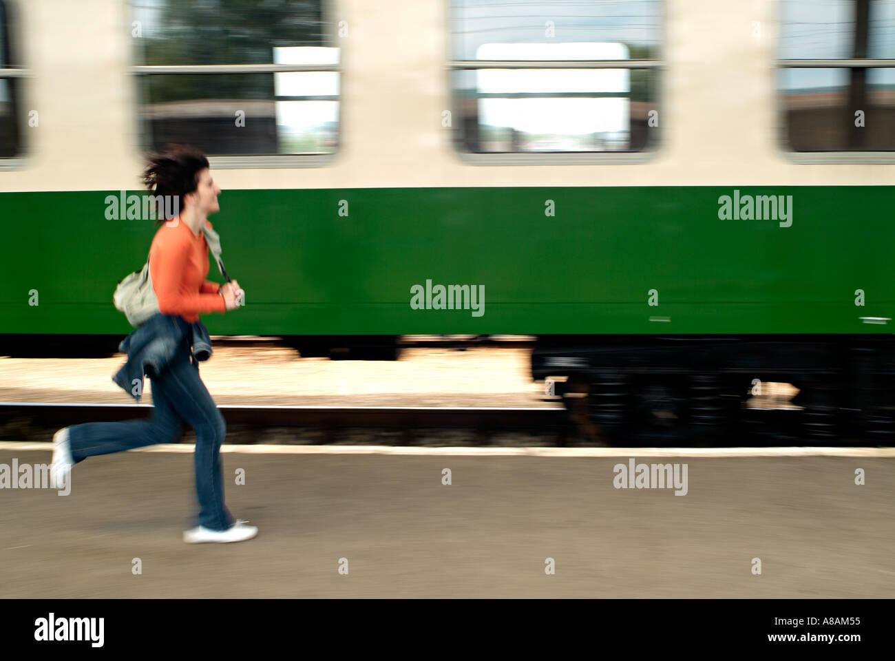 Woman Running Along a Train Station Platform Trying to Catch a Departing Train - Stock Image