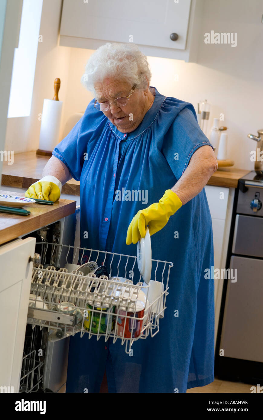 Independent elderly lady loading her dishwasher in her modern home kitchen - Stock Image