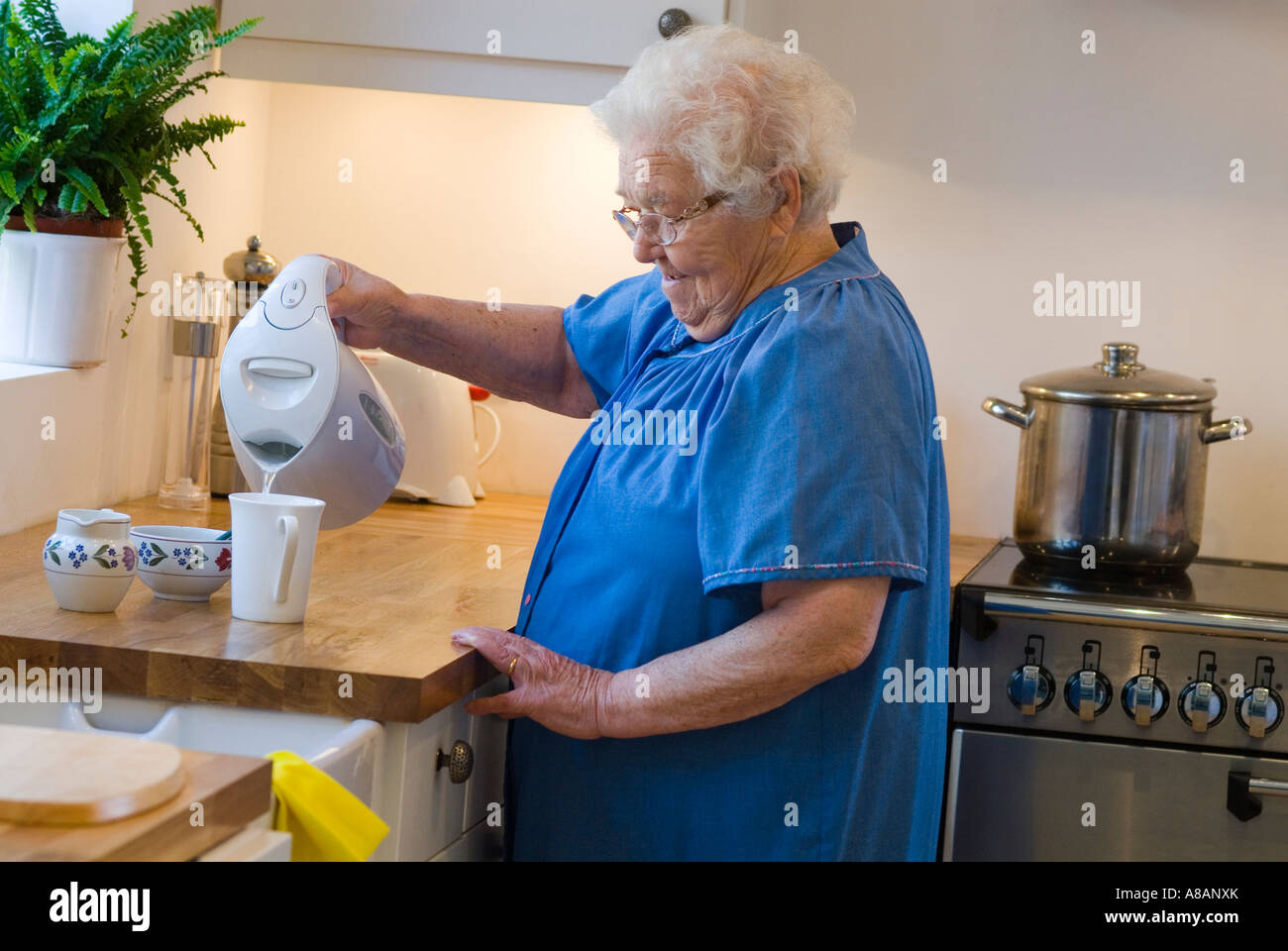 Independent elderly lady making a cup of tea in her modern home kitchen - Stock Image