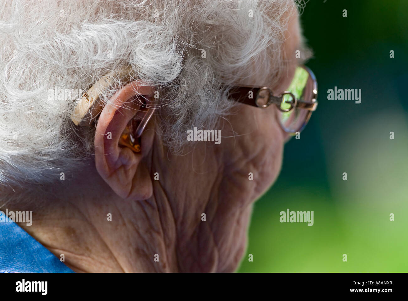 Elderly lady wearing hearing aid and glasses - Stock Image