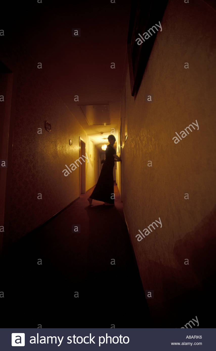 Woman standing in a shadowy corridor at night - Stock Image