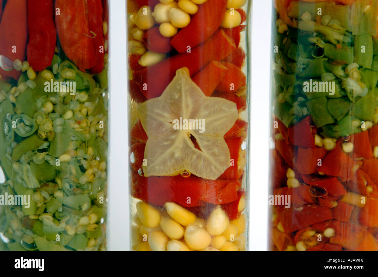 Mixed pickled vegetables preserved in glass jars - Stock Image