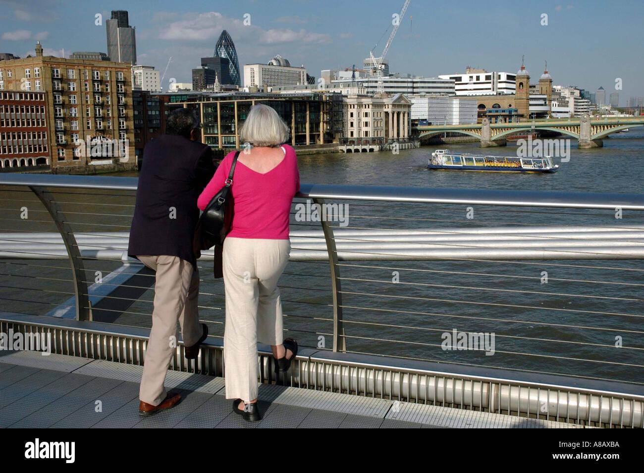 COUPLE GAZE AT THE THAMES LONDON UK FROM THE MELLINIUM BRIDGE - Stock Image