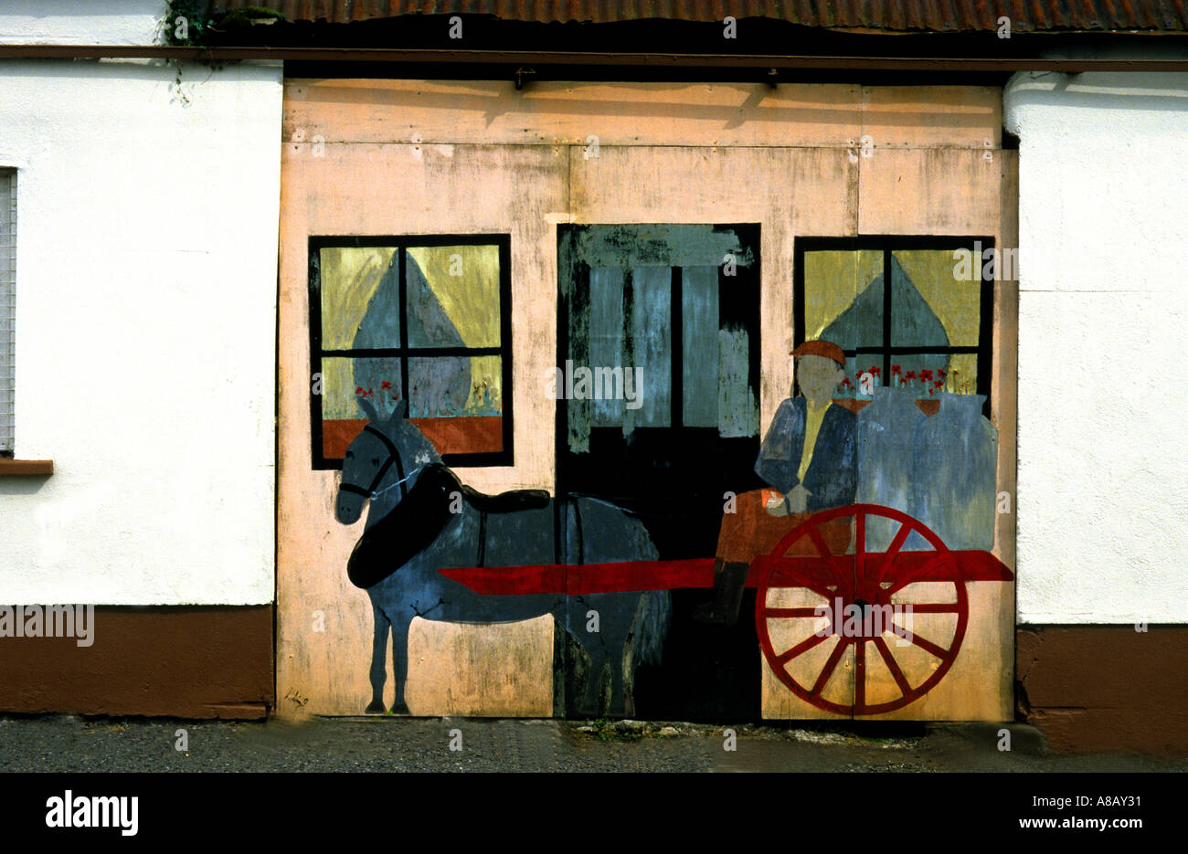PRIMATIVE  BUT CHARMING  WALL PAINTING ON A GARAGE DOOR IN IRELAND FEATURING DONKEY AND CART - Stock Image