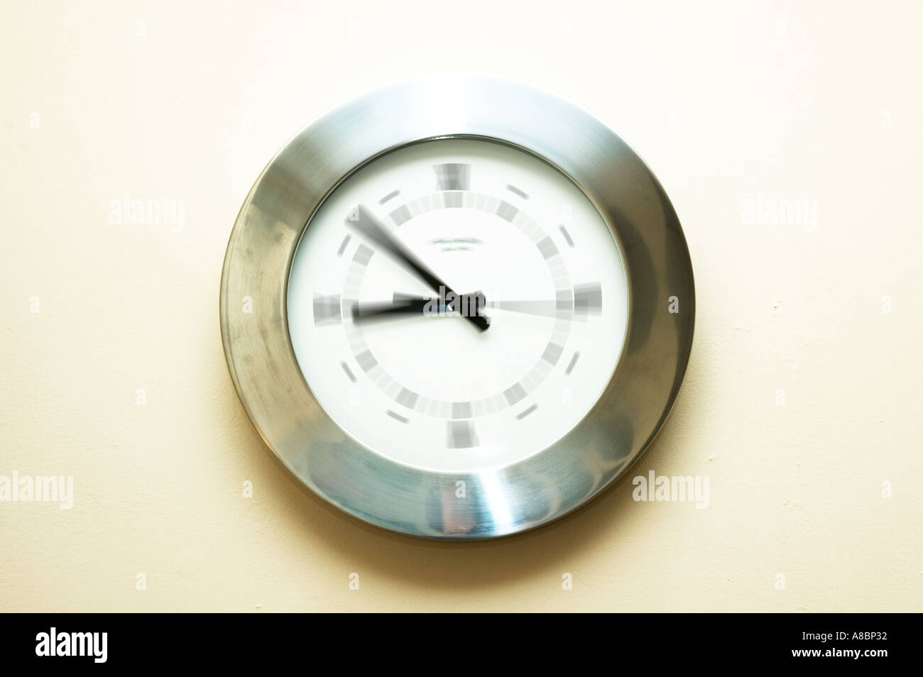 silver analogue clock on the wall with white background - Stock Image