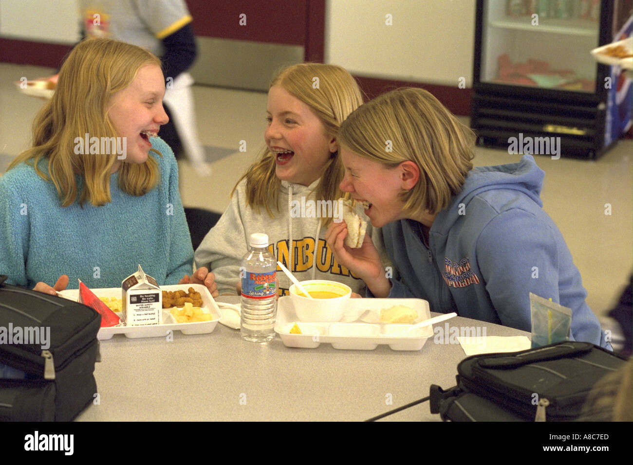 Girls age 14 laughing hysterically during school lunch period. Golden Valley Minnesota USA - Stock Image