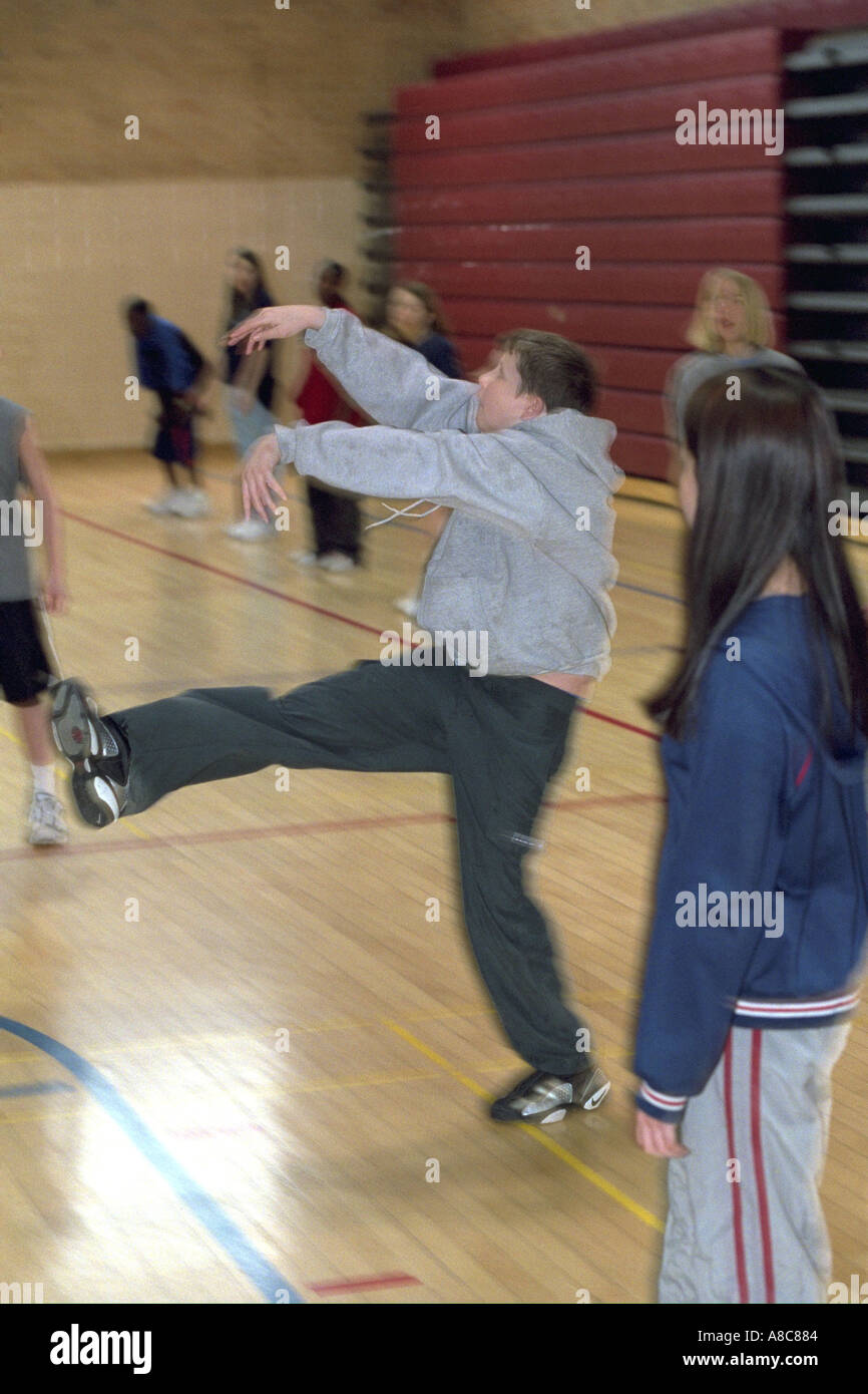 Student hitting volleyball over net age 14. Golden Valley Minnesota USA Stock Photo