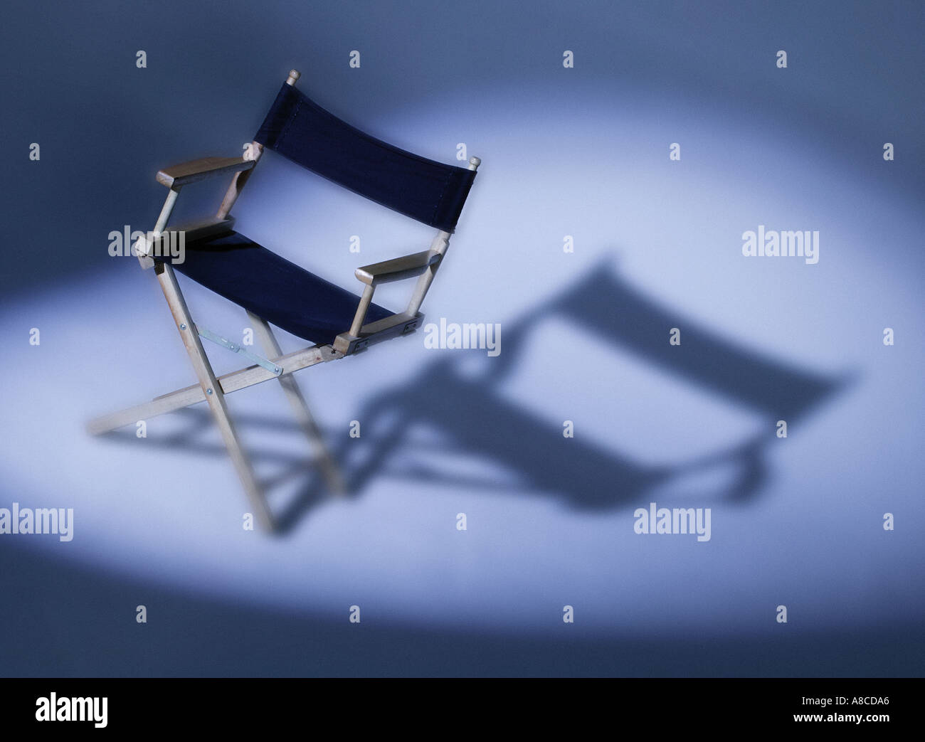 FOLDING WOOD AND CANVAS FILM DIRECTORS CHAIR IN SPOTLIGHT BEAM - Stock Image