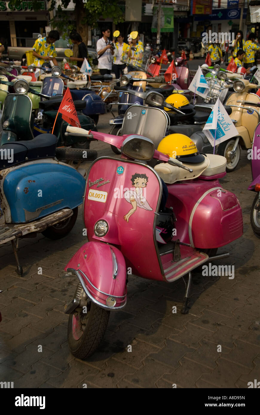Pink Vespa With Yellow Helmet On The Seat Parked With Others Stock Photo Alamy