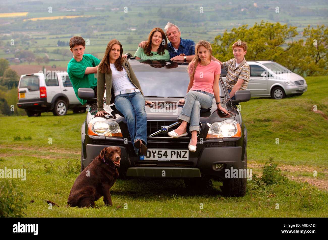 A FAMILY WITH TEENAGE CHILDREN SITTING ON A VOLVO XC90 UK - Stock Image