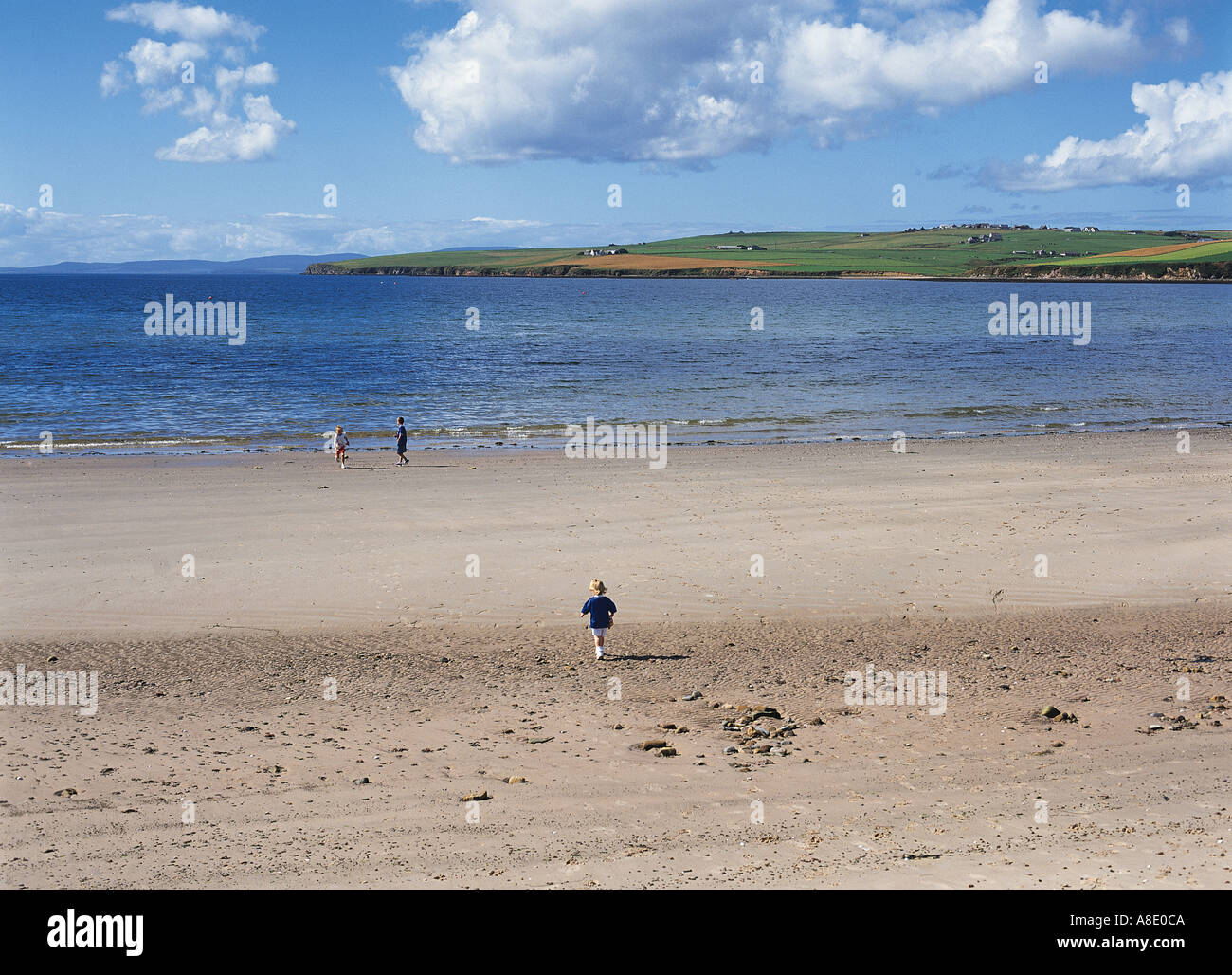 dh Scapa beach SCAPA BAY ORKNEY Scotland Three children white sandy beach holiday kids child playing sea uk Stock Photo