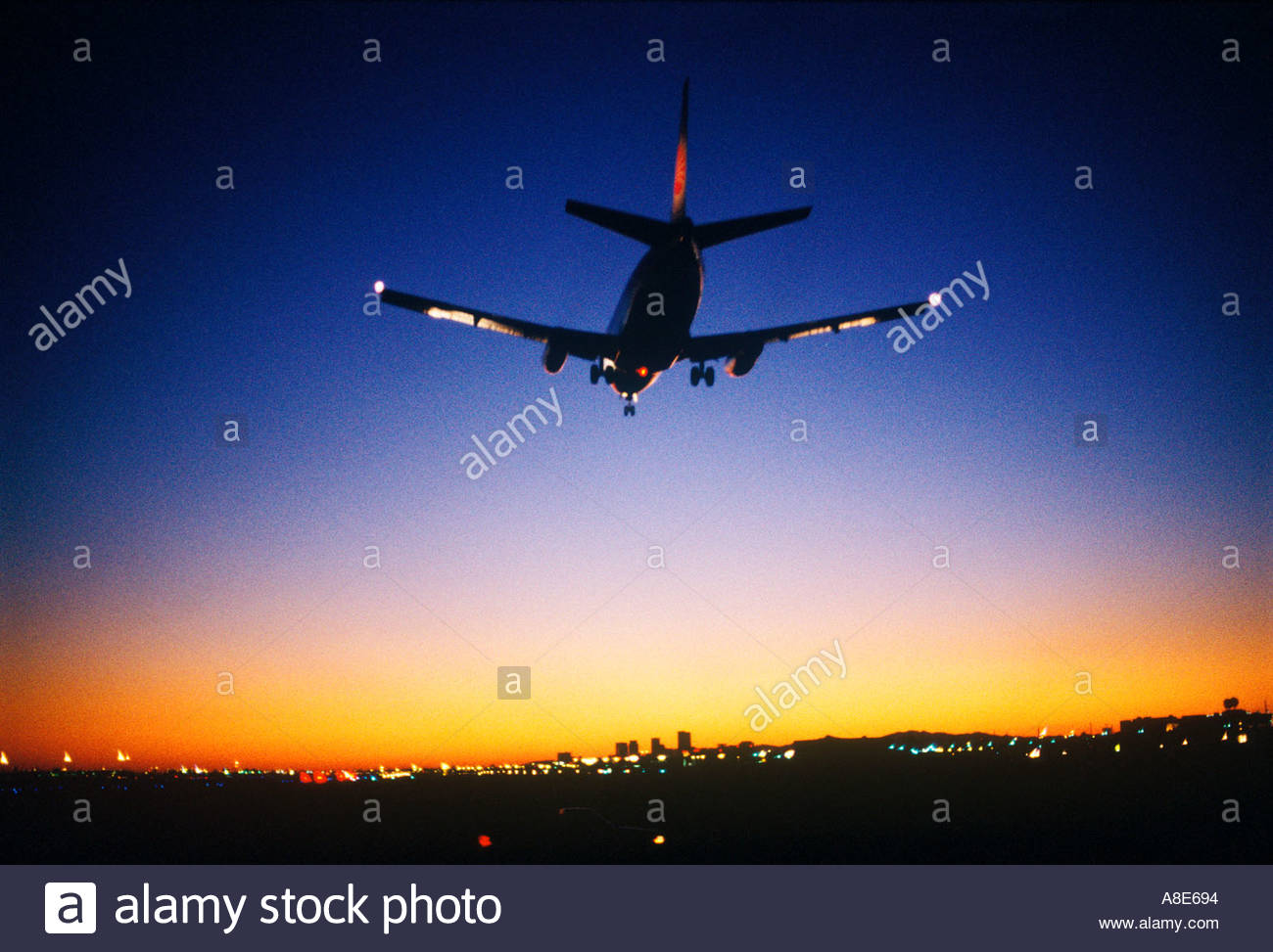 Commercial Airliner landing at Phoenix International Airport at Dusk   tall buildings of Phoenix can be seen in the background - Stock Image