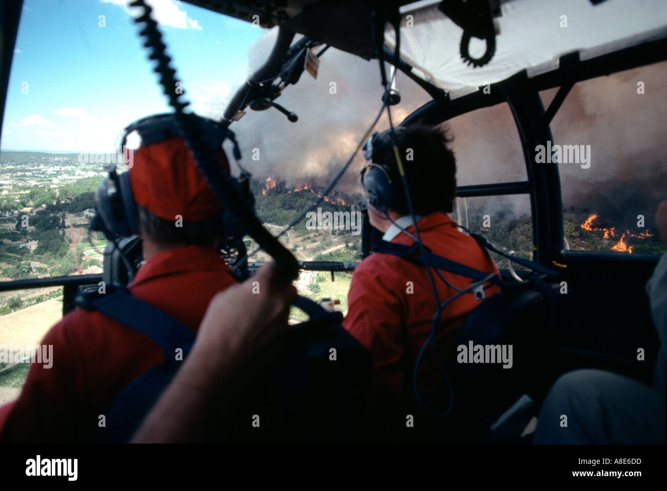 Pilots Inside Cockpit Of Firefighters Alouette III Helicopter In Flight Over A Wildfire Provence France