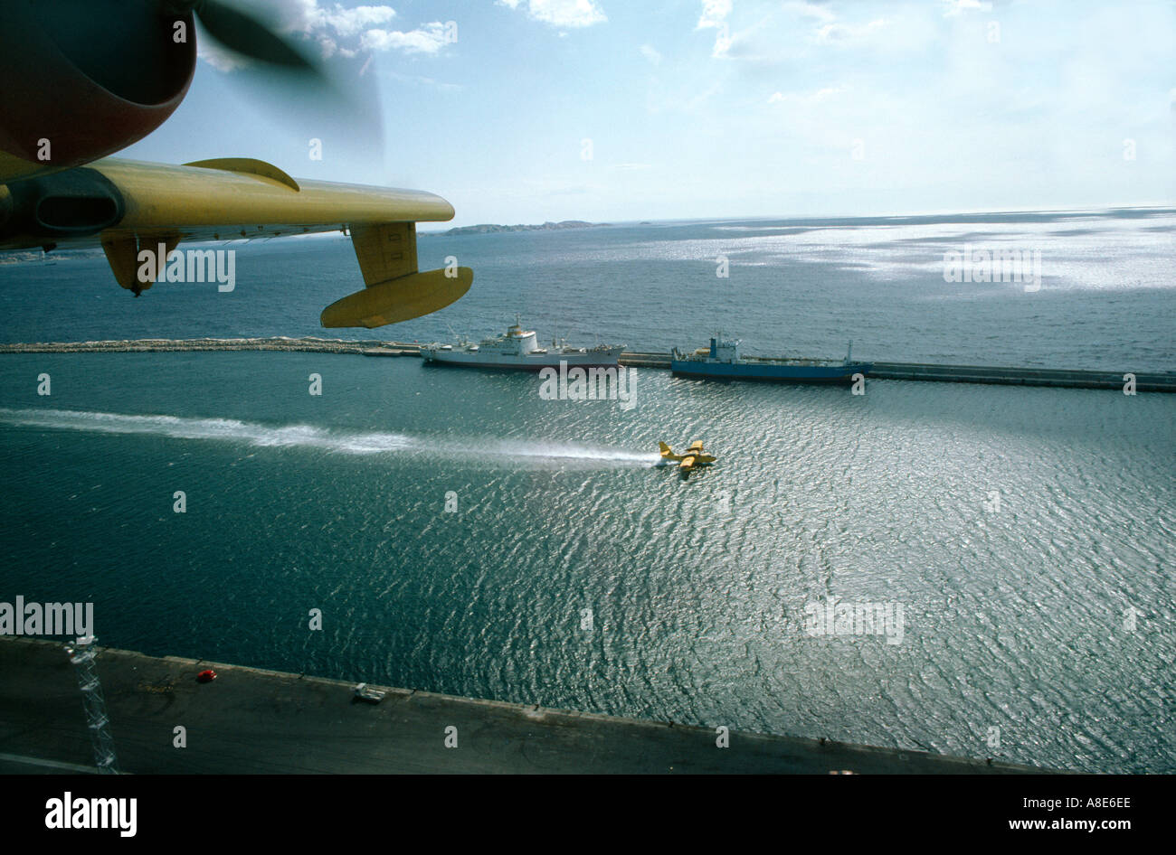 Aerial view of a Canadair firefighting water bomber airplane scooping water from sea, harbour, Provence, France, Stock Photo