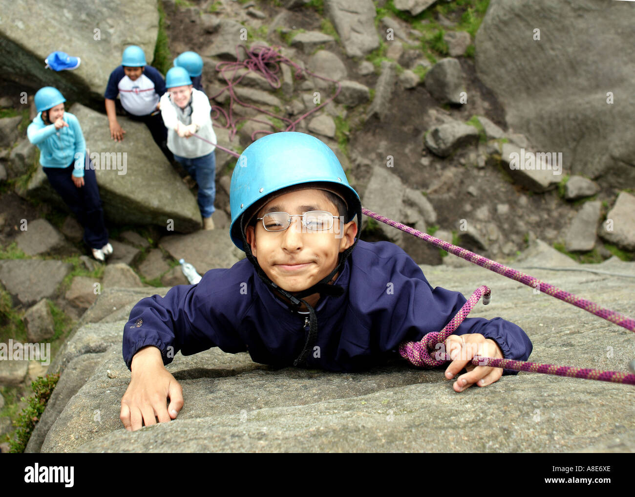 A disabled child rock climbing while on a school trip in the Peak District - Stock Image