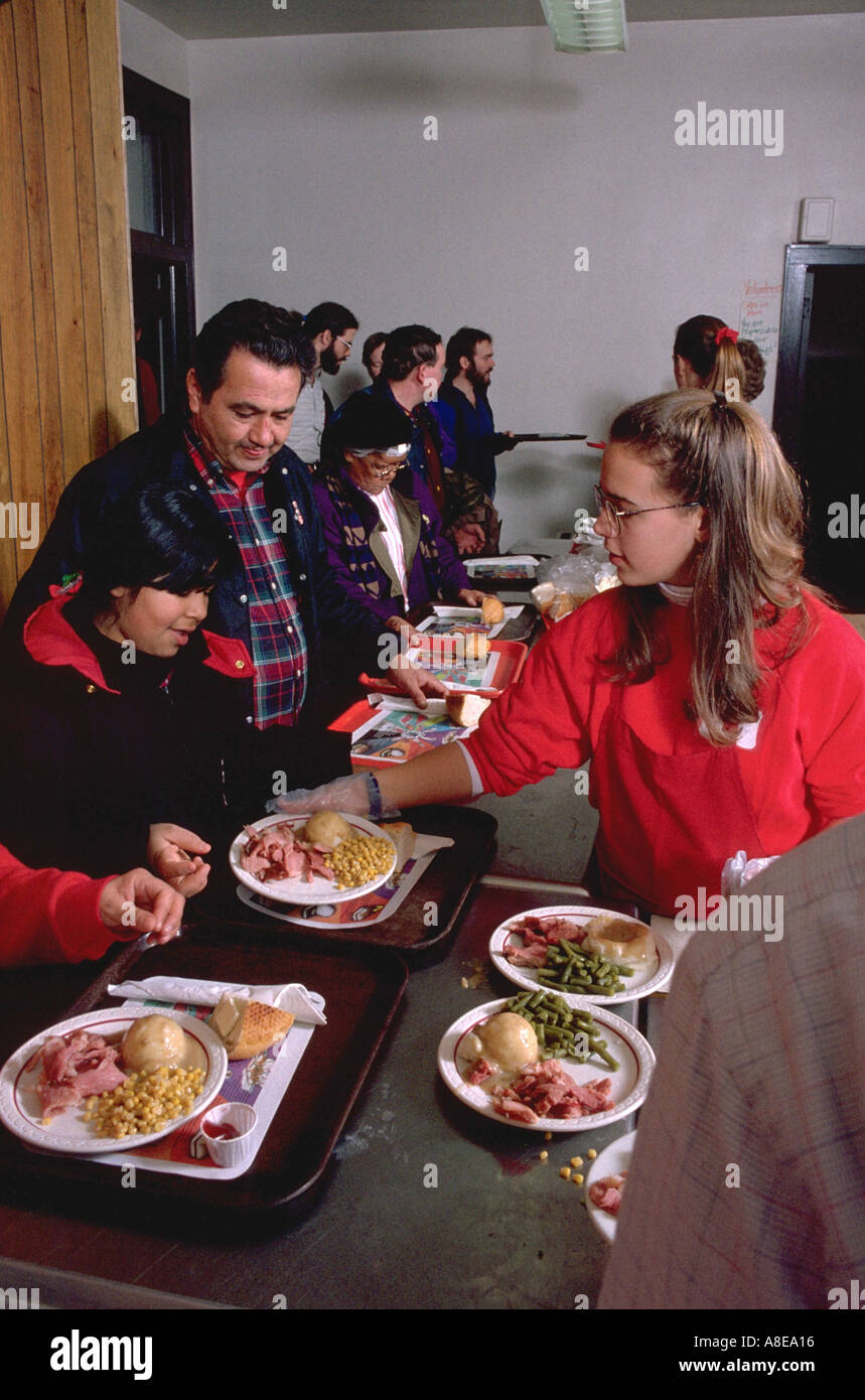Teen serving couple Christmas dinner in church soup kitchen Stock ...