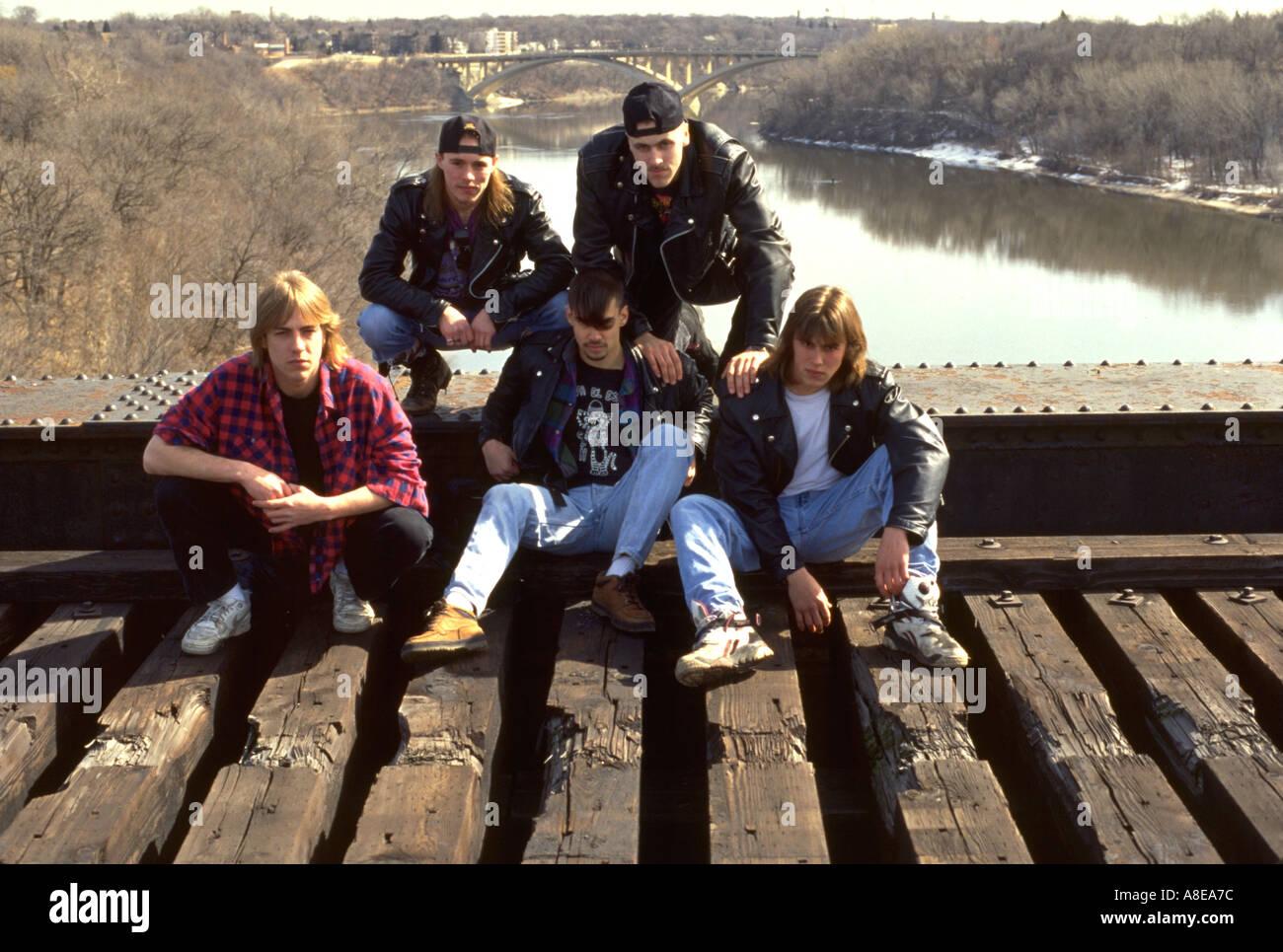 Members of rock band ages 18 thru 20 sitting on railroad bridge. St Paul Minnesota USA - Stock Image