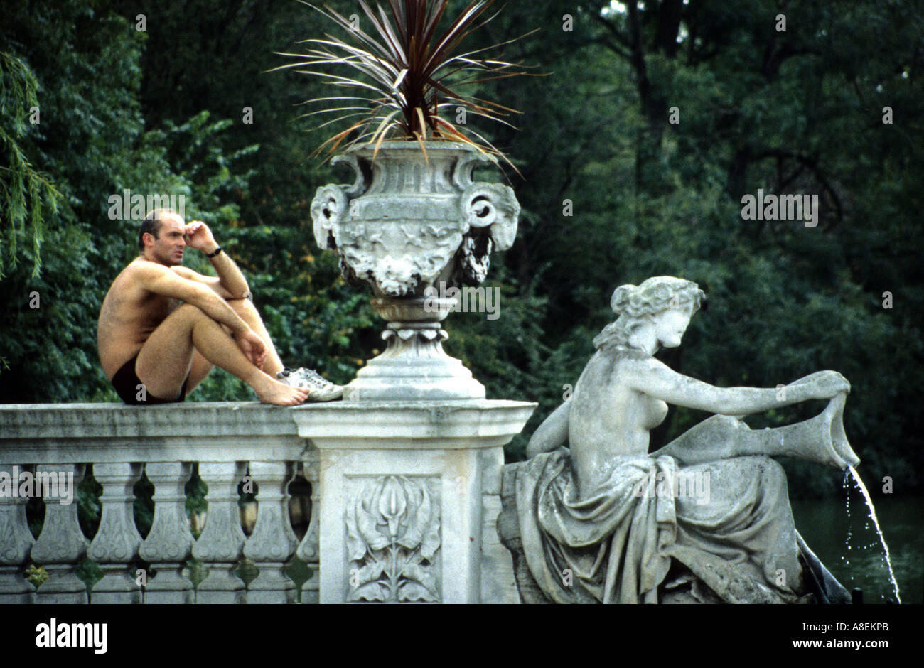 Male sunbather strikes matching pose with statue, Regents Park, London - Stock Image