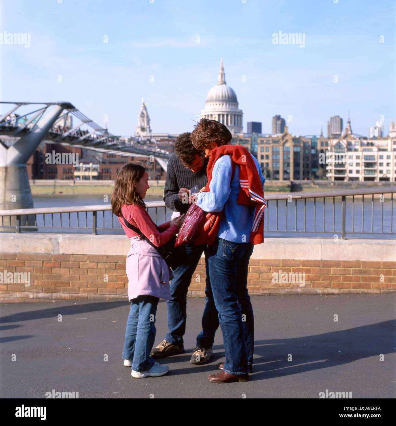 A family on a day out looking at a map by the Millennium Bridge, South Bank, London England UK    KATHY DEWITT Stock Photo