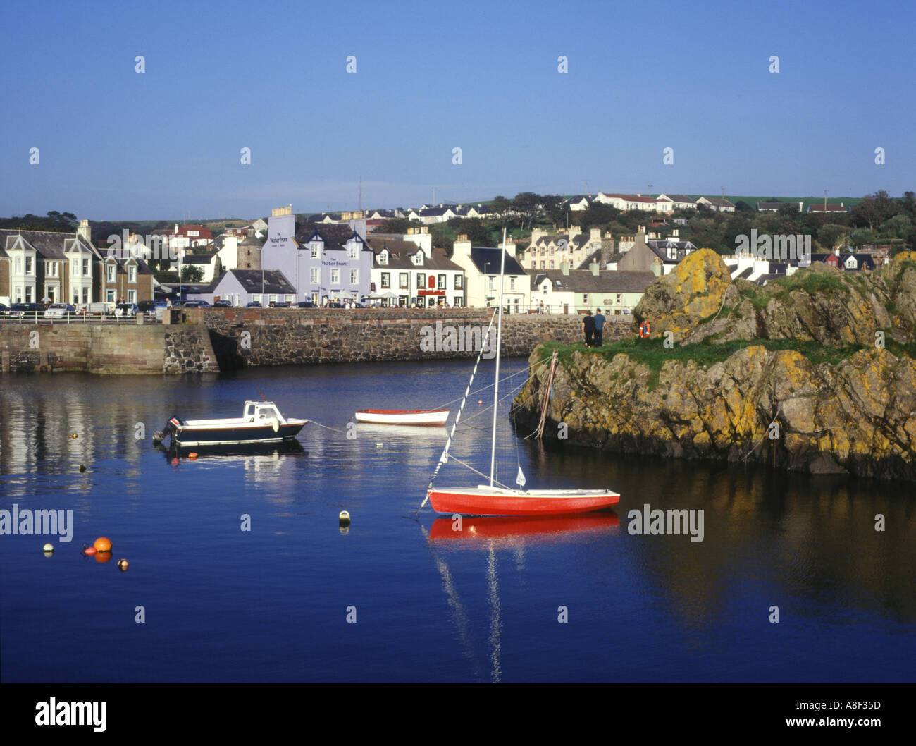 dh Harbour PORTPATRICK DUMFRIES Couple people sailing motor boats waterfront sea Stock Photo