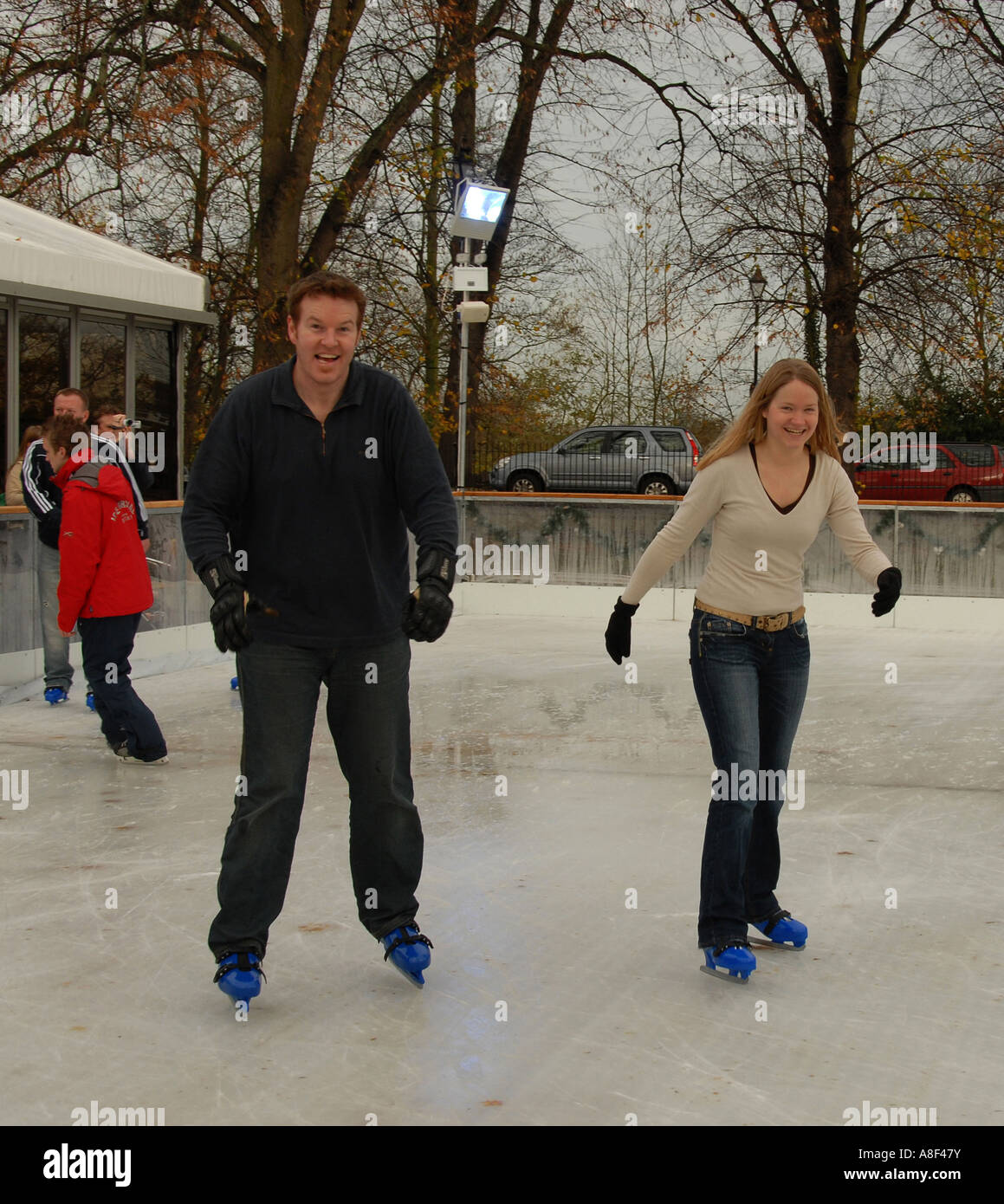 Visitors to Windsor, England, having fun on a temporary skating rink close to Windsor Castle - Stock Image